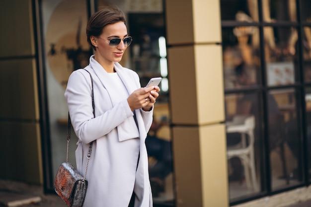 Jovem, mulher negócio, em, agasalho, usando, telefone