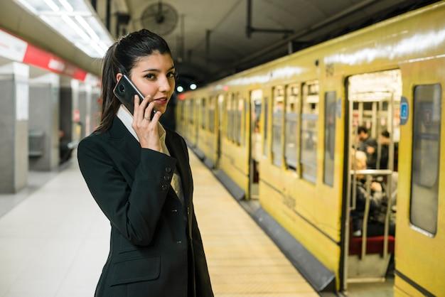 Jovem, mulher negócios fica, em, estação metrô, falando telefone móvel