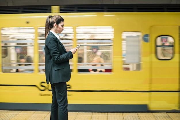 Jovem, mulher negócios fica, frente, movimento, trem metrô, usando, telefone móvel