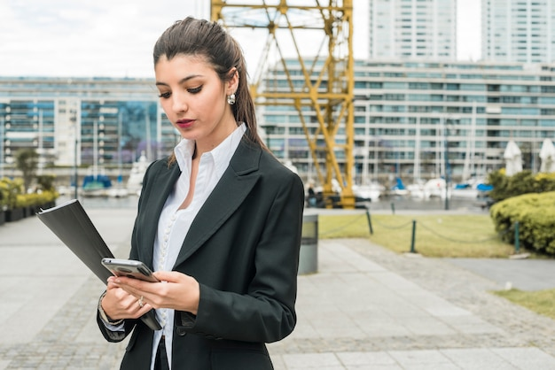 Jovem, mulher negócios fica, frente, predios, usando, telefone móvel