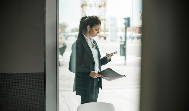 Jovem, mulher negócios, ficar, exterior, a, porta vidro, usando, telefone móvel