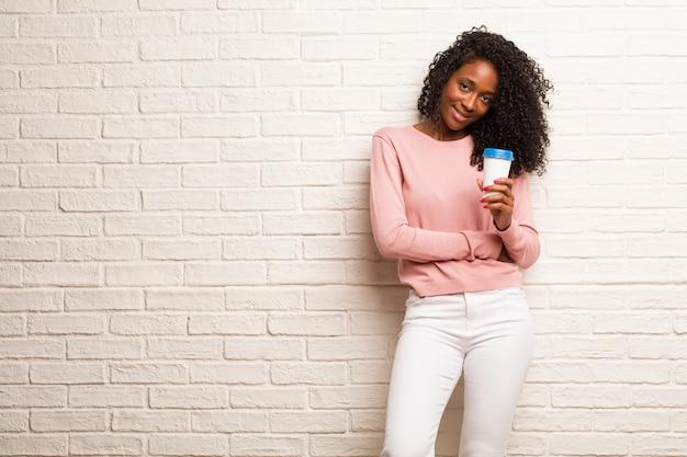 Jovem mulher negra alegre e com um grande sorriso, confiante