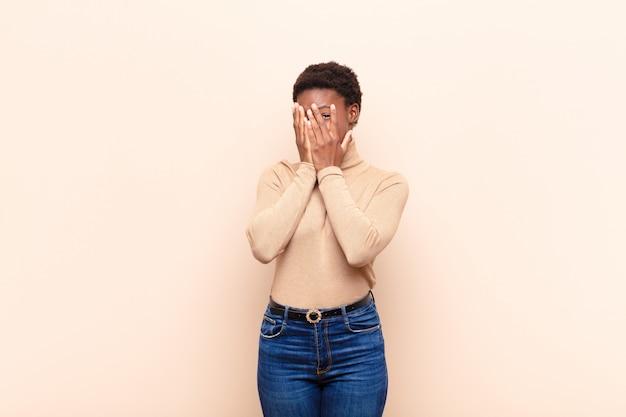 Jovem mulher negra bonita, cobrindo o rosto com as mãos, espreitando entre os dedos com expressão de surpresa e olhando para o lado
