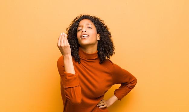 Jovem mulher negra bonita fazendo gesto de capice ou dinheiro, dizendo para você pagar suas dívidas! contra parede laranja