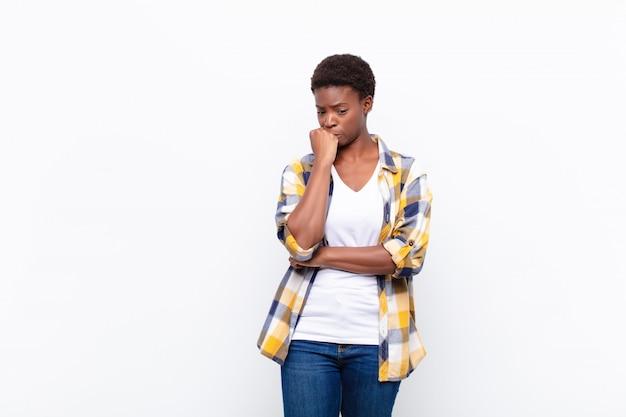 Jovem mulher negra bonita se sentindo sério, pensativo e preocupado, olhando de soslaio com a mão pressionada contra o queixo