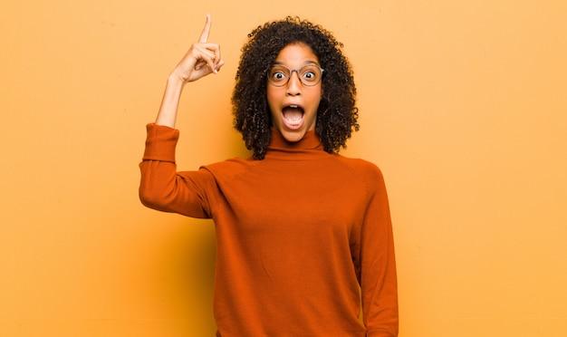 Jovem mulher negra bonita se sentindo um gênio feliz e animado depois de realizar uma idéia, alegremente levantando o dedo, eureka! contra parede laranja
