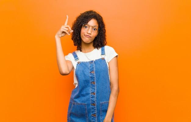 Jovem mulher negra bonita se sentindo um gênio segurando o dedo orgulhosamente no ar depois de perceber uma ótima idéia, dizendo eureka contra a parede laranja