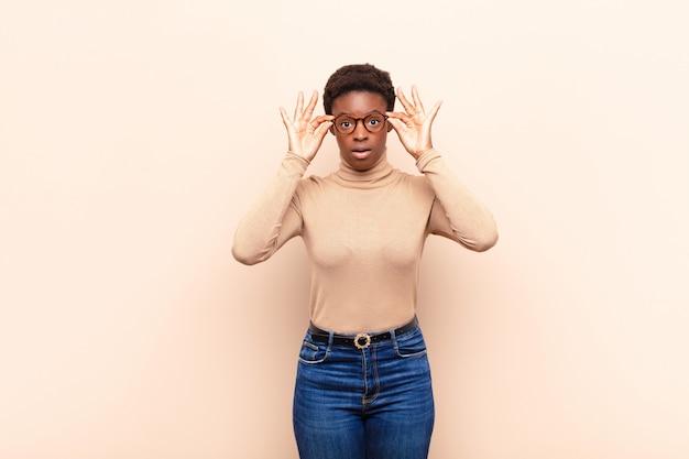 Jovem mulher negra bonita, sentindo-se chocado, surpreso e surpreso, segurando os óculos com um olhar atônito e incrédulo