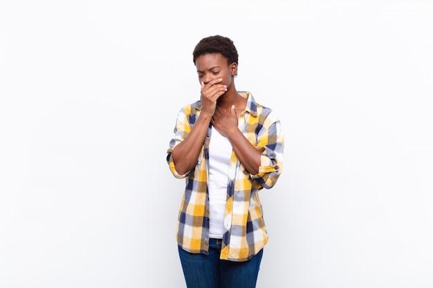 Jovem mulher negra bonita, sentindo-se doente com sintomas de dor de garganta e gripe, tosse com a boca coberta