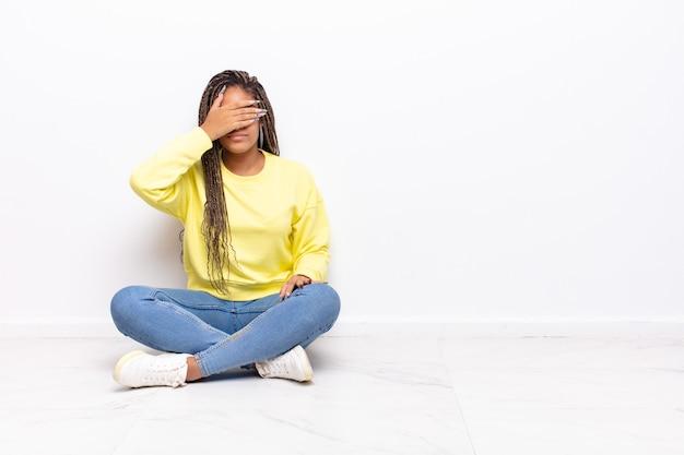 Jovem mulher negra cobrindo os olhos com uma das mãos, sentindo-se assustada ou ansiosa, pensando ou esperando cegamente por uma surpresa