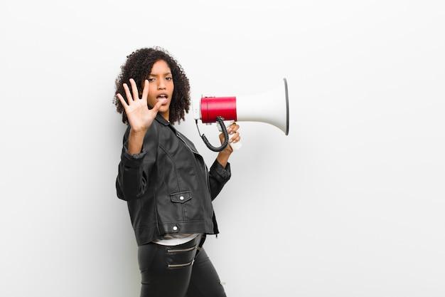 Jovem mulher negra com um megafone, vestindo uma jaqueta de couro contra branco