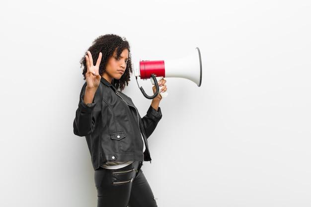 Jovem mulher negra com um megafone, vestindo uma jaqueta de couro contra parede branca