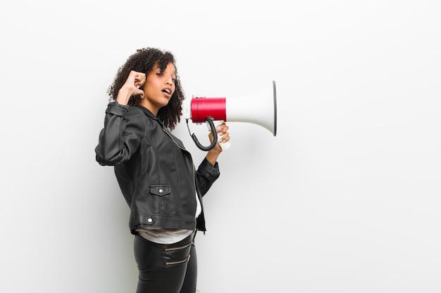 Jovem mulher negra com um megafone, vestindo uma jaqueta de couro na parede branca