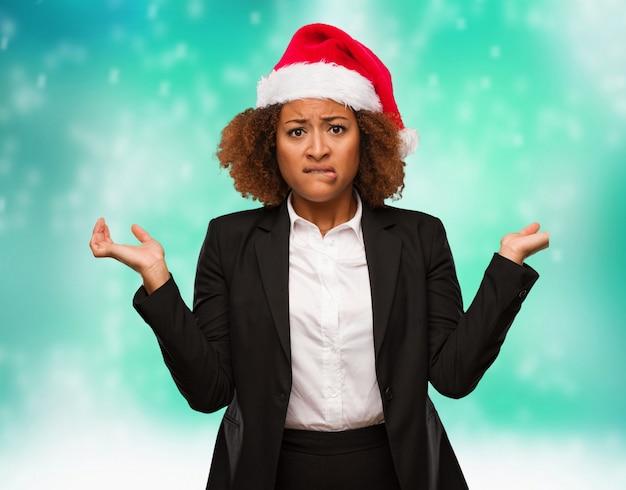 Jovem mulher negra de negócios usando um chapéu de papai noel chirstmas confuso e duvidoso