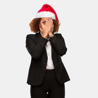Jovem mulher negra de negócios usando um chapéu de papai noel chirstmas se sente preocupado e com medo