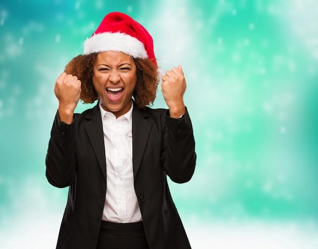 Jovem mulher negra de negócios usando um chapéu de papai noel chirstmas surpreso e chocado