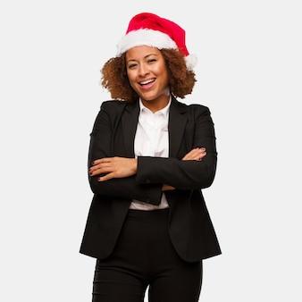 Jovem mulher negra de negócios usando um chirstmas santa chapéu cruzando braços, sorrindo e relaxado