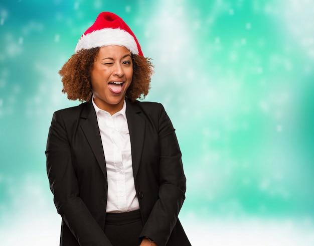 Jovem mulher negra de negócios usando um chirstmas santa chapéu funnny e amigável mostrando a língua