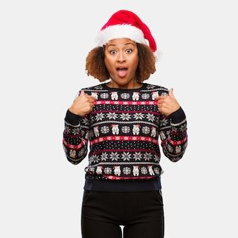 Jovem mulher negra em uma camisola de natal da moda com impressão de surpresa, sente-se bem sucedida