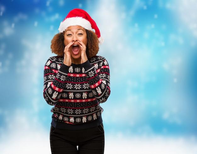 Jovem mulher negra em uma camisola de natal na moda com impressão gritando algo feliz para a frente