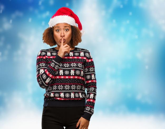 Jovem mulher negra em uma camisola de natal na moda com impressão, mantendo um segredo ou pedindo silêncio