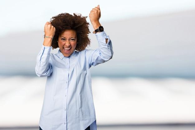Jovem mulher negra fazendo um gesto de vencedor