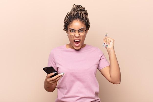 Jovem mulher negra gritando agressivamente com uma expressão de raiva ou com os punhos cerrados celebrando o sucesso. conceito de telefone inteligente