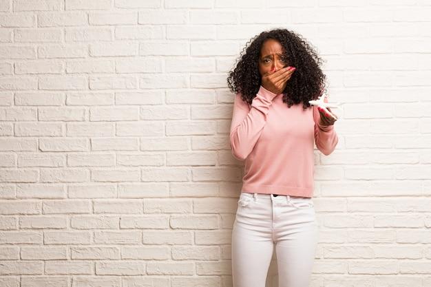 Jovem mulher negra muito assustada e com medo, desesperada por algo, gritos de sofrimento e de olhos abertos, conceito de loucura