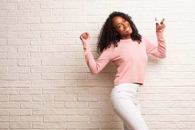 Jovem mulher negra muito feliz e animada, levantando os braços, celebrando uma vitória ou sucesso, ganhando na loteria