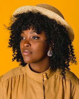 Jovem mulher negra no chapéu de palha a desviar o olhar