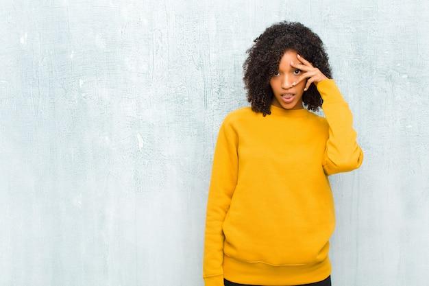 Jovem mulher negra olhando chocado, assustado ou aterrorizado, cobrindo o rosto com a mão e espreitando entre os dedos