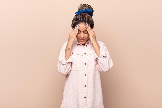 Jovem mulher negra parecendo estressada e frustrada, trabalhando sob pressão, com dor de cabeça e preocupada com problemas