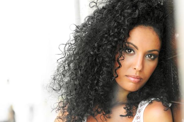 Jovem, mulher negra, penteado afro, em fundo urbano