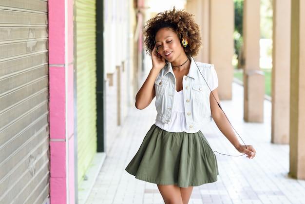 Jovem, mulher negra, penteado afro, em rua urbana com fones de ouvido