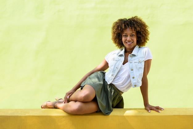 Jovem, mulher negra, penteado afro, sentado em uma parede urbana