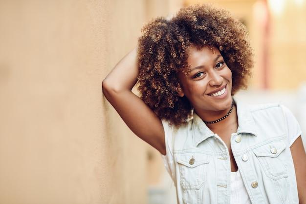 Jovem, mulher negra, penteado afro, sorrindo em fundo urbano