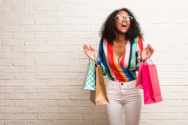 Jovem mulher negra rindo e se divertindo, sendo relaxada e alegre, se sente confiante e bem sucedida