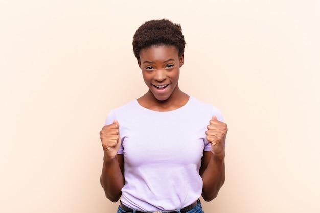 Jovem mulher negra se sentindo chocado, animado e feliz, rindo e comemorando o sucesso, dizendo uau!