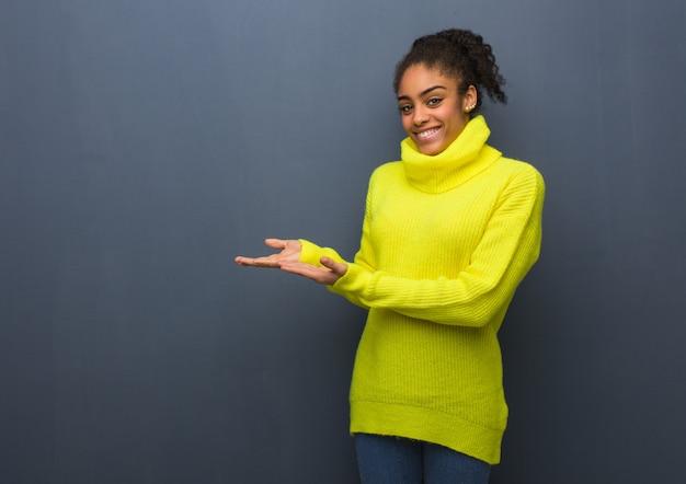 Jovem mulher negra segurando algo com as mãos