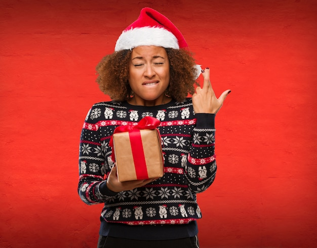 Jovem mulher negra segurando um presente no dia de natal, cruzando os dedos por ter sorte