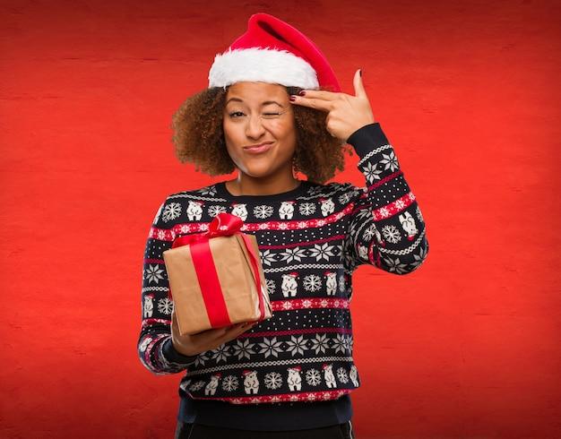 Jovem mulher negra segurando um presente no dia de natal, fazendo um gesto de suicídio