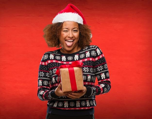 Jovem mulher negra segurando um presente no dia de natal funnny e amigável mostrando a língua