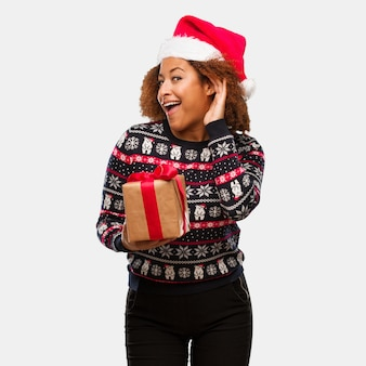 Jovem mulher negra segurando um presente no dia de natal tentar ouvir uma fofoca