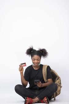 Jovem mulher negra, sentada com as pernas cruzadas, usando seu telefone celular e cartão de crédito