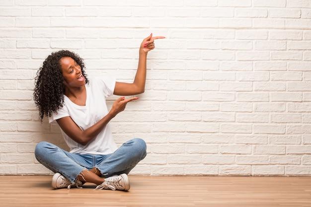 Jovem mulher negra sentada num chão de madeira, apontando para o lado