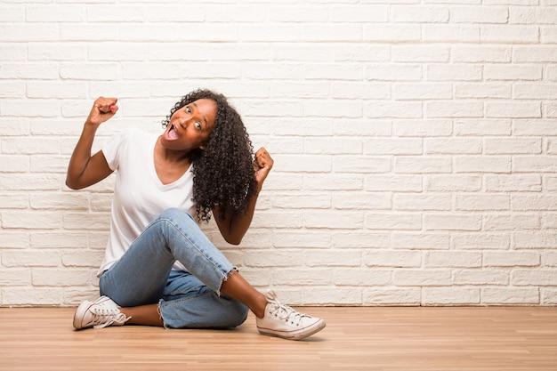 Jovem mulher negra sentada num chão de madeira muito feliz e animado, levantando os braços
