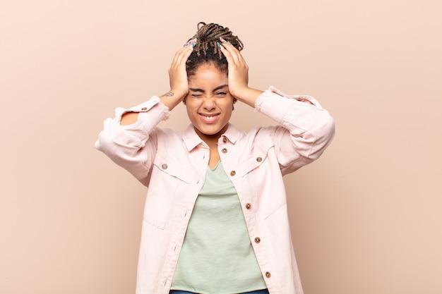 Jovem mulher negra sentindo-se estressada e ansiosa, deprimida e frustrada com uma dor de cabeça, levando as duas mãos à cabeça