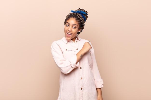 Jovem mulher negra sentindo-se feliz, positiva e bem-sucedida, motivada para enfrentar um desafio ou comemorar bons resultados