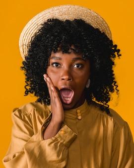 Jovem mulher negra surpresa com a boca aberta