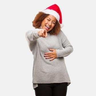 Jovem mulher negra usando um chapéu de papai noel sonha em alcançar objetivos e propósitos